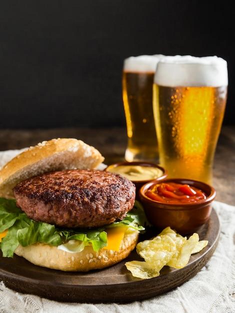 Hambúrguer saboroso com copos de cerveja Foto Premium