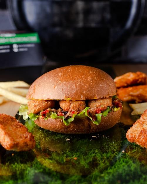 Hambúrguer suculento com nuggets de frango em massa Foto gratuita