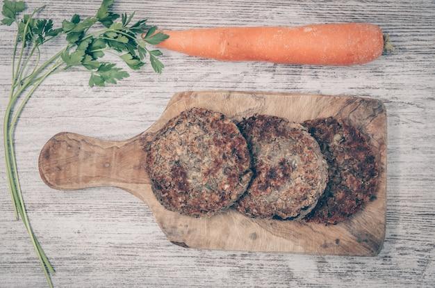 Hambúrguer vegano com lentilhas. prato vegetariano saudável. fundo de madeira Foto Premium