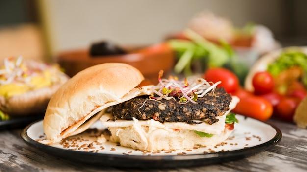 Hambúrguer vegetariano de quinoa com brotos e sementes de linho na chapa branca Foto gratuita