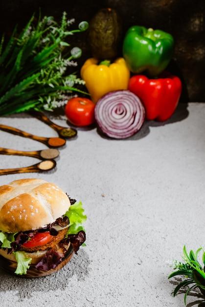 Hambúrguer vegetariano na superfície de madeira com legumes. comida vegetariana saudável. seitan, soja Foto Premium