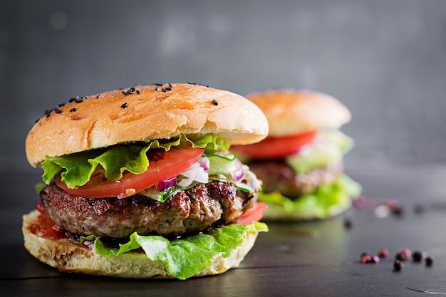 Hambúrgueres com carne, tomate, cebola roxa e alface Foto gratuita