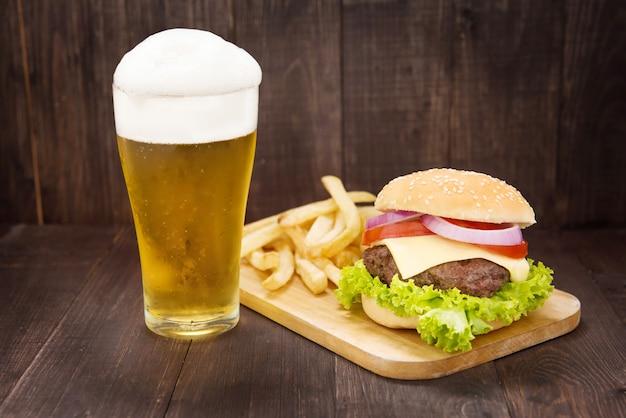 Hambúrgueres com cerveja na mesa de madeira Foto Premium
