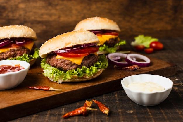 Hambúrgueres com ketchup na bandeja de madeira Foto gratuita