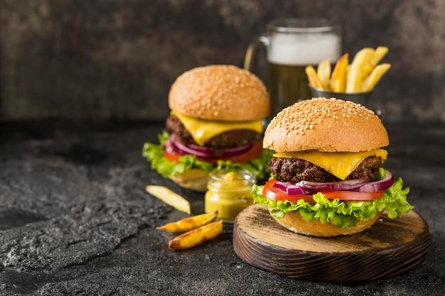 Hambúrgueres de alto ângulo com batata frita, molho e cerveja com cópia-espaço Foto gratuita