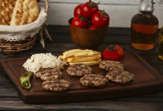 Hambúrgueres de carne de bovino servidos com batata frita, arroz e legumes grelhados Foto gratuita