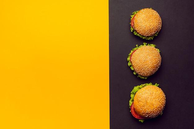 Hambúrgueres de configuração plana com espaço para texto Foto gratuita