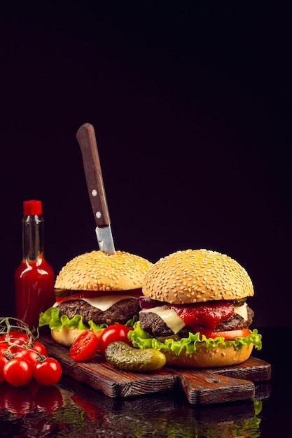 Hambúrgueres de vista frontal na placa de corte Foto gratuita