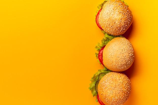 Hambúrgueres de vista superior em fundo laranja Foto gratuita