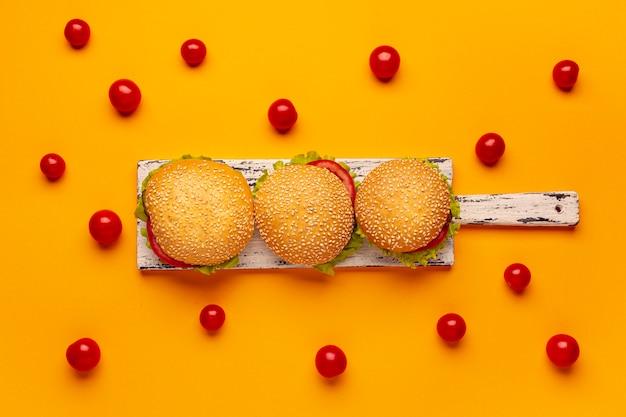 Hambúrgueres de vista superior na placa de corte Foto gratuita