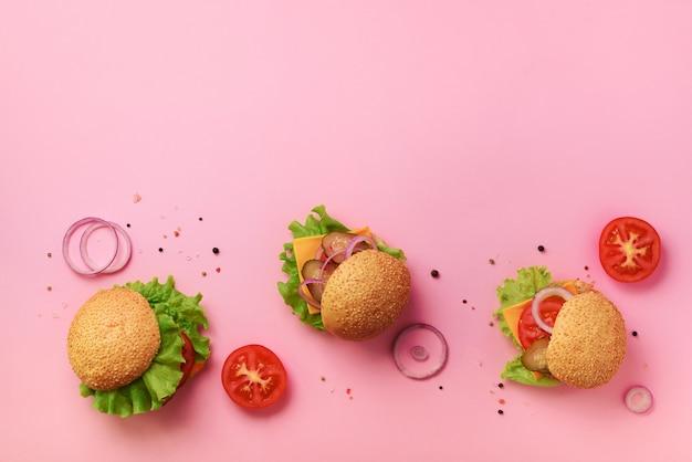 Hambúrgueres saborosos com carne, tomate, queijo, cebola, pepino e alface no fundo rosa. Foto Premium