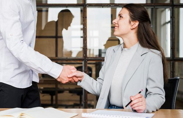 Handshake de linda mulher de negócios com seu colega Foto gratuita