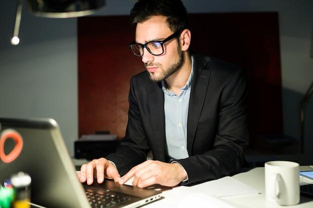 Handsome jovem empresário trabalhando com laptop no escritório. Foto gratuita