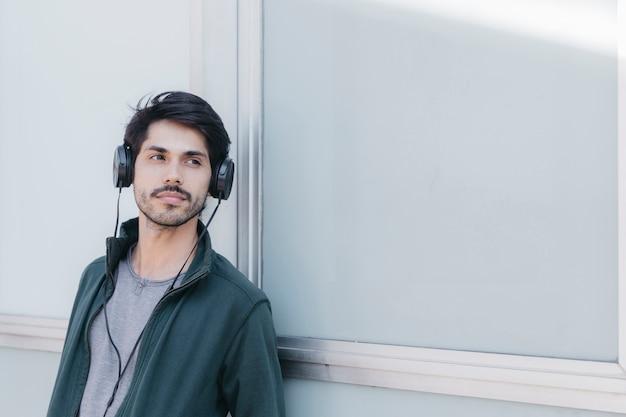 Handsome young man em fones de ouvido fora Foto gratuita