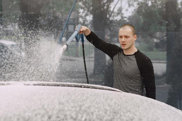 Handsomen homem em um suéter preto lavando seu carro Foto gratuita