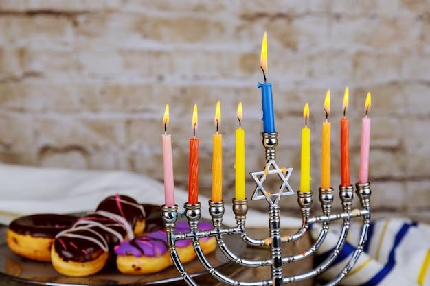 Hanukkah flatlay: hanukkah doces sufganiyot, menorah, velas multicoloridas Foto Premium