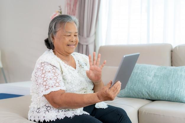 Happy hour virtual de mulher idosa asiática, conhecer e conversar on-line com a filha em videoconferência com tablet digital para uma reunião on-line em vídeo chamada para distanciamento social. Foto Premium