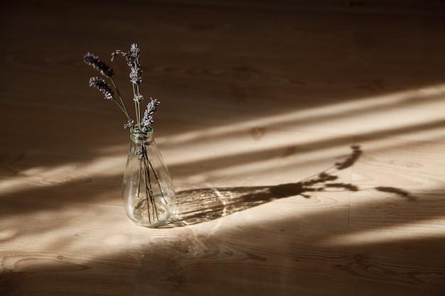 Hastes de lavanda em uma garrafa de vidro à luz do sol Foto Premium