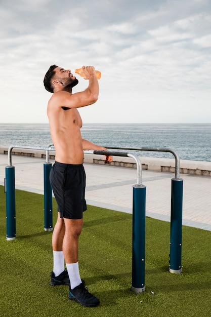 Hidratação masculina nova após o exercício Foto gratuita