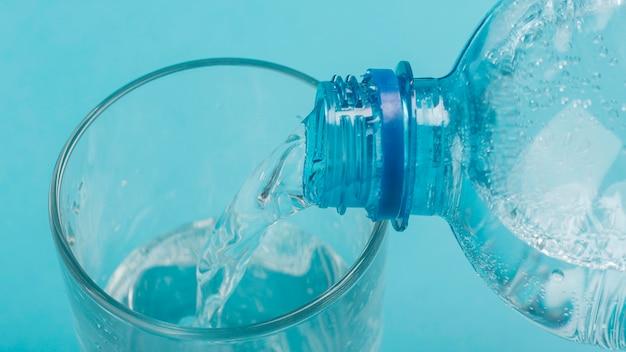 High view derramando água com gás em um copo Foto gratuita