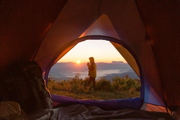 Hiker, levantar, em, a, acampamento, frente, laranja, barraca, e, mochila, em, a, montanhas Foto gratuita