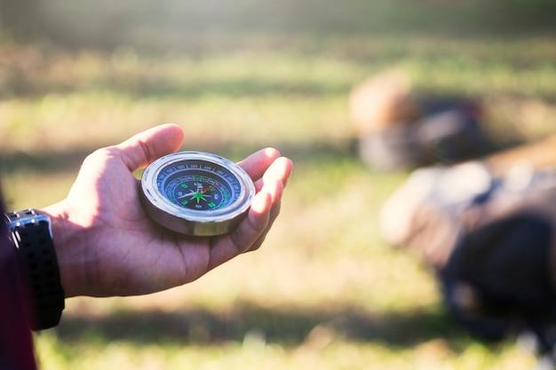Hiker procurando direção com uma bússola na floresta. Foto gratuita