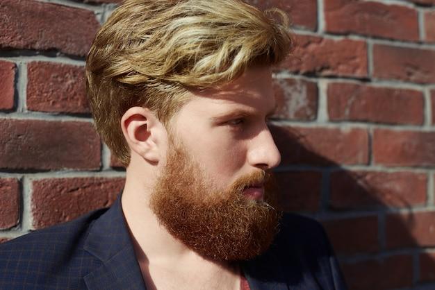 Hipster barbudo bonito com emoção séria na parede de tijolo vermelho Foto gratuita