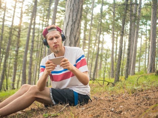 Hipster barbudo louco em casual e boné sente-se na floresta de natureza com telefone e fones de ouvido jogando jogos no smartphone Foto Premium