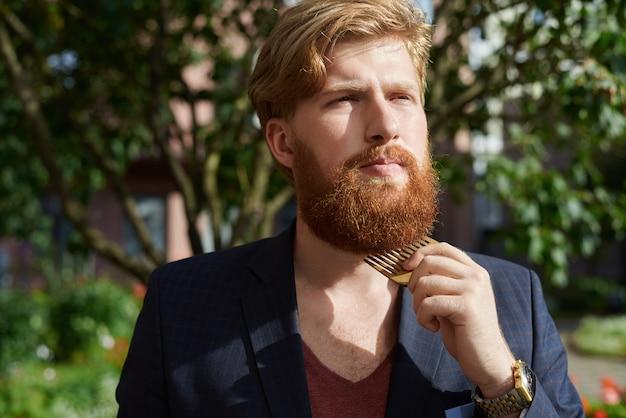 Hipster barbudo vermelho no verão caminhando e penteando a barba Foto gratuita
