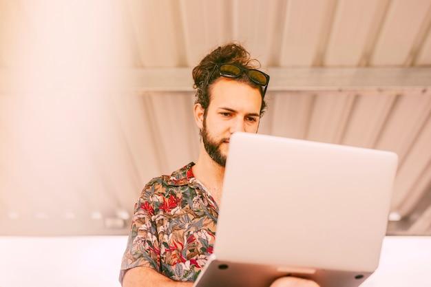 Hipster concentrado trabalhando no laptop ao ar livre Foto gratuita
