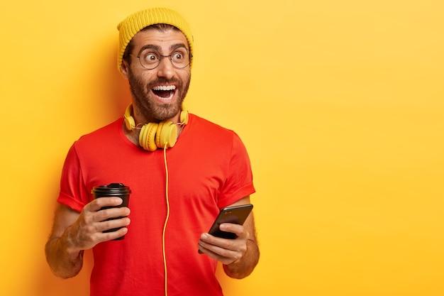 Hipster feliz em traje casual segurando uma xícara de café e um celular Foto gratuita