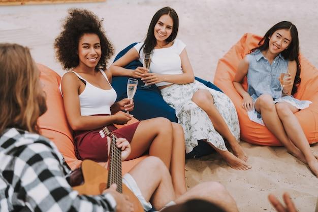 Hipster homem tocando violão na praia meninas sorrindo Foto Premium