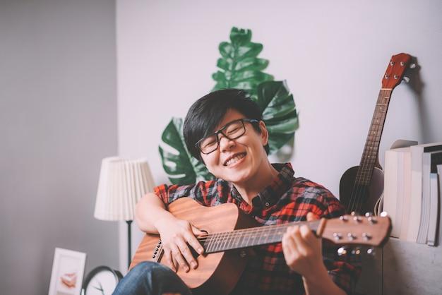 Hipster jovem tocando guitarra em casa para relaxar em casa, sala de estar Foto Premium