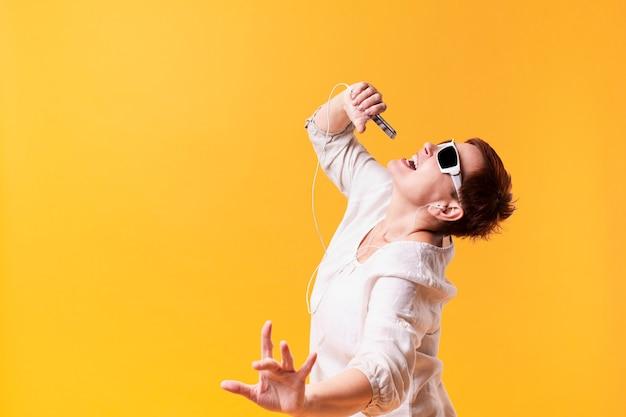 Hipster mulher sênior dançando e cantando Foto gratuita