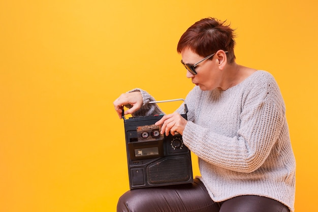 Hipster mulher sênior segurando um toca-fitas vintage Foto gratuita