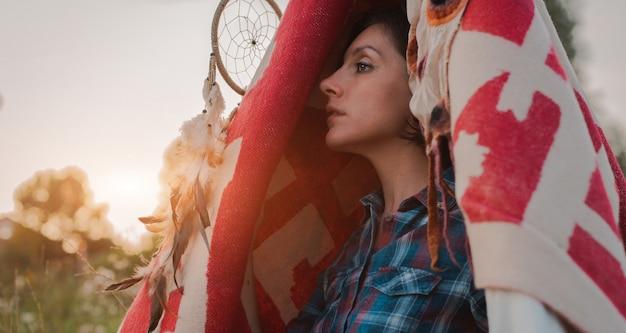 Hipster mulher sob a forma de um xamã está à procura de inspiração da mãe terra em um wigwam na natureza. Foto Premium