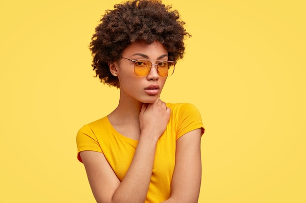 Hipster sério e agradável com penteado afro Foto gratuita