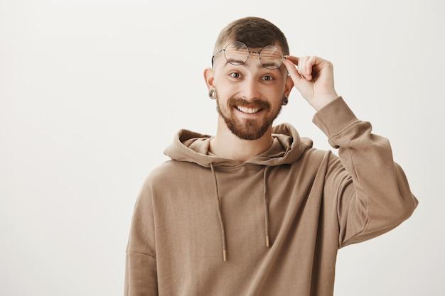 Hipster surpreso com barba, sorriso feliz e óculos de decolagem Foto gratuita