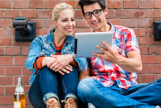 Hipster turistas planejando férias de berlim com computador de almofada Foto Premium