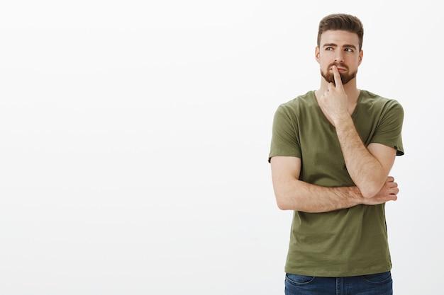 Hmm, pode funcionar. retrato de um homem fazendo um plano e tomando uma decisão em mente, parado em uma pose pensativa, tocando o lábio com o dedo enquanto pensa, olhando determinado no canto superior esquerdo, escolhendo Foto gratuita