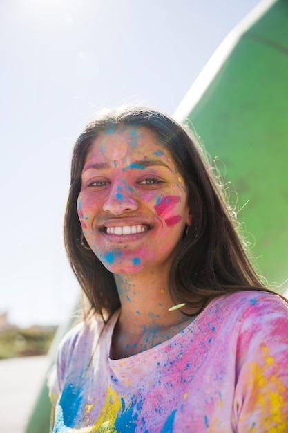 Holi cor em pó sobre o rosto da jovem sorridente, olhando para a câmera Foto gratuita