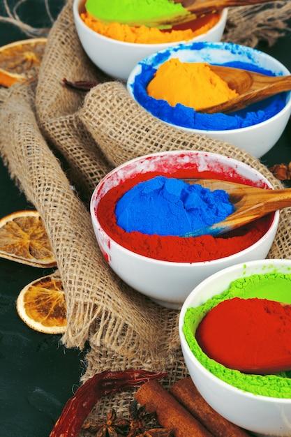 Holi indiano tradicional cores em pó, especiarias no fundo rústico escuro Foto Premium