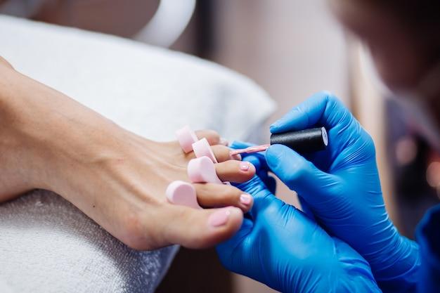 Home salon pedicure tratamento de pés e unhas o processo de pedicure profissional mestre em luvas azuis aplique esmalte de gel rosa claro Foto gratuita