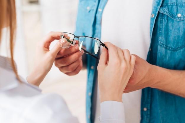 Homem à procura de novos óculos no optometrista Foto gratuita