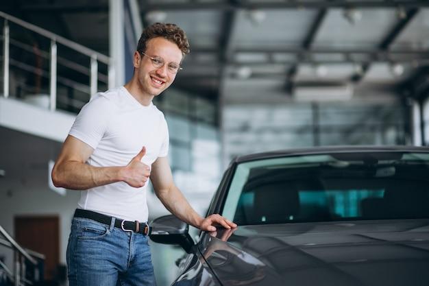 Homem à procura de um carro em um showroom de carro Foto gratuita