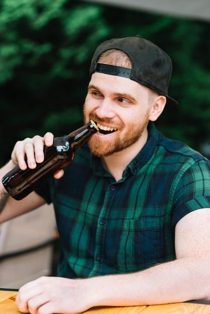 Homem, abertura, a, garrafa cerveja, boné, com, seu, dentes Foto gratuita
