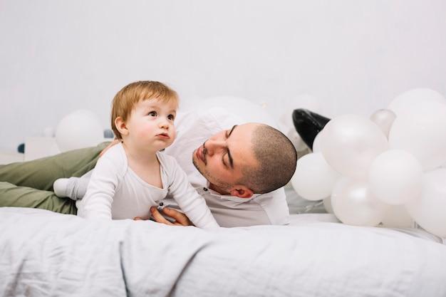 Homem, abraçando, pequeno, bebê cama, perto, balões Foto gratuita