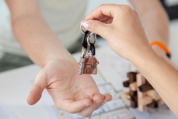 Homem aceitando as chaves para um close de casa nova Foto gratuita