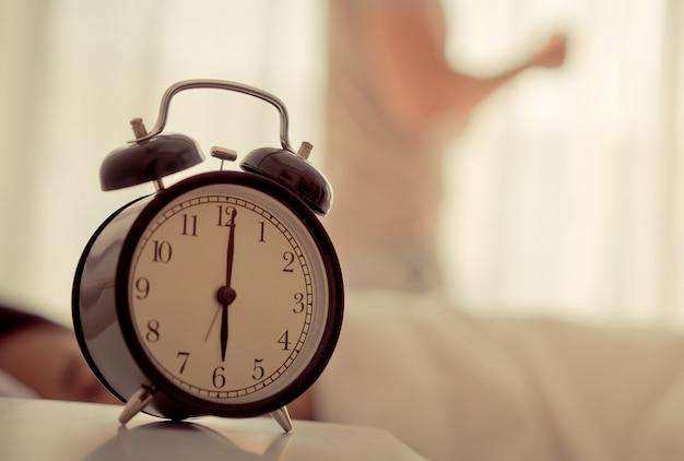 Homem acordou cedo o relógio mostrando 6 horas Foto Premium