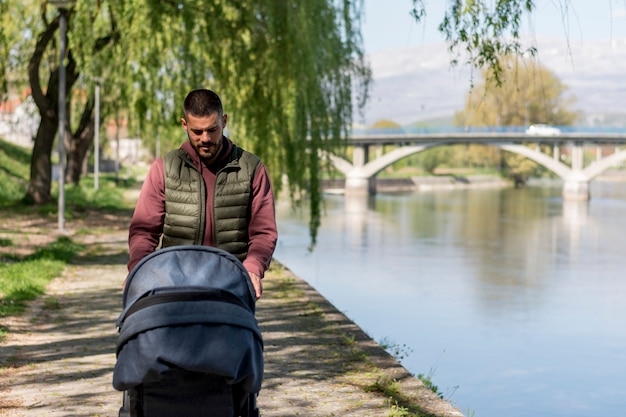 Homem adulto, andar, com, carrinho bebê, perto, rio Foto gratuita